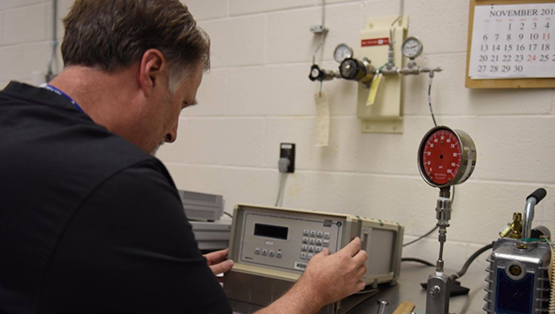John Isel, 30th Space Wing Precision Measurement Equipment Laboratory quality assurance evaluator, adjusts a pressure gauge, Nov. 17, 2016, Vandenberg Air Force Base, Calif. The PMEL directly impacts mission success by ensuring continuity across the base for all measurement apparatus. (U.S. Air Force photo by Senior Airman Ian Dudley/Released)