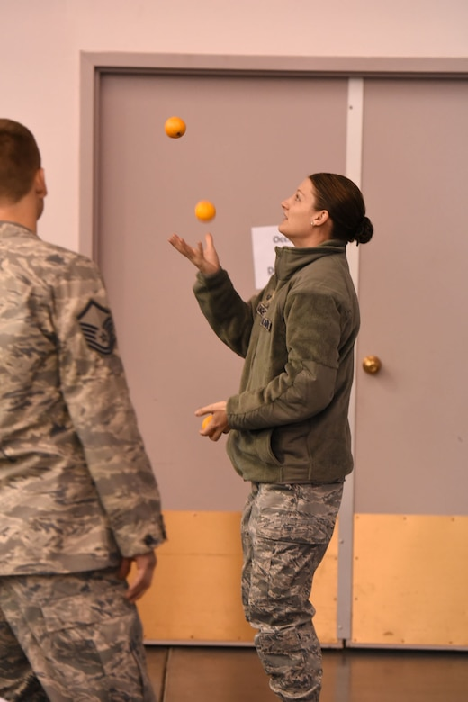 Tech. Sgt. Amanda McKnight, a 120th Security Forces Squadron security forces specialist, juggles oranges during a crowd participation exercise during the 120th Airlift Wing's 2016 Wingman Day event December 3, 2016 at the Mansfield Center in Great Falls, Montana. The crowd participation exercise required individuals to share with their groups some unique fact about themselves. (U.S. Air National Guard photo/Master Sgt. Michael Touchette)