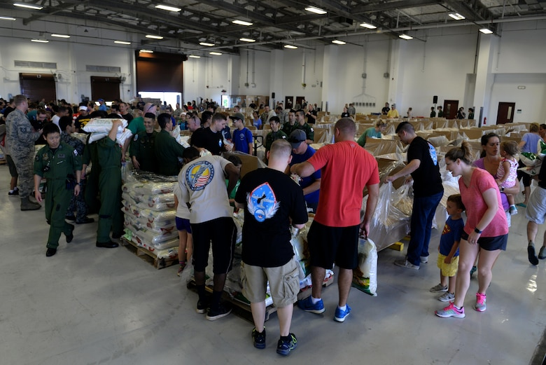Operation Christmas Drop volunteers pack boxes Dec. 3, 2016, at Andersen Air Force Base, Guam. Over 200 volunteers packed clothes, rice, fish hooks, school supplies and more to be dropped over 50 islands throughout the Pacific. (U.S. Air Force photo by SrA Alexa Henderson/Released)