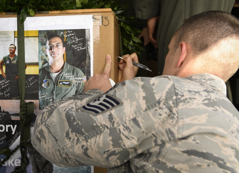 An Airman participating in Operation Christmas Drop signs the memorial aerial delivery bundle for Senior Airman Jeremy Jutba-Hake, 36th Airlift Squadron instructor loadmaster, at Andersen Air Force Base, Guam, Dec. 6, 2016. The 36 AS dropped Jutba-Hake's memorial bundle, filled with donated supplies, on the Micronesian island of Satawal. After the drop, the island's entire population of 600 stood on the beach to wave and thank the passing aircrew. (U.S. Air Force photo by Senior Airman Elizabeth Baker/Released)