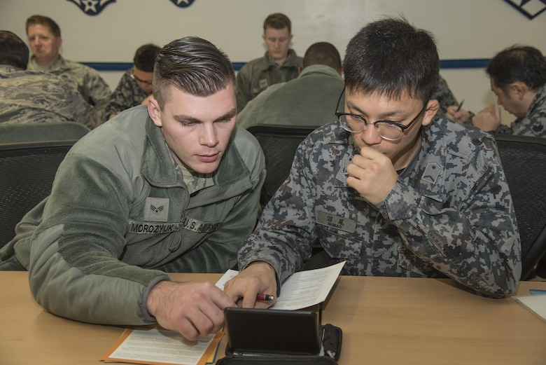 "U.S. Air Force Senior Airman Kostyantyn Morozyuk, a 14th Aircraft Maintenance Unit crew chief, works with Japan Air Self-Defense Force Staff Sgt. Tomoyuki Numao, a 3rd Air Wing crew chief, during a ""4 Lenses"" exercise at Misawa Air Base, Japan, Nov. 30, 2016. The ""4 Lenses"" test is a proven personality assessment which helps organizations build understanding of the innate talent and potential of its individuals. Airmen and JASDF members were given a chance to work around language barriers while getting to know each other prior to working together during a bilateral exchange. (U.S. Air Force photo by Airman 1st Class Sadie Colbert)"