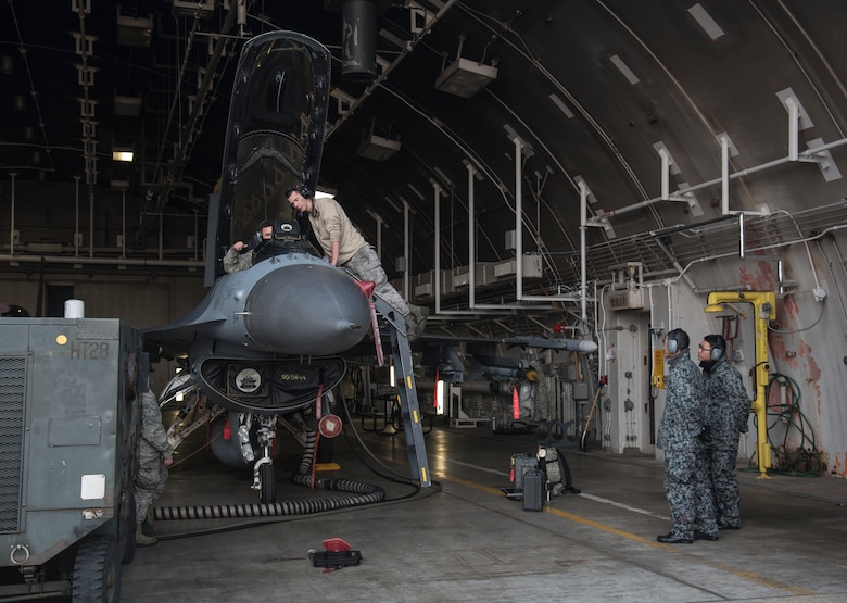 U.S. Air Forec Airman 1st Class Glenn Koontz, left, and Senior Airman Corey Robinson, center right, both 14th Aircraft Maintenance Unit electrical and environmental technicians, work on an F-16 Fighting Falcon as Japan Air Self-Defense Force Staff Sgts. Narihito Tanaka, center left, and Kenta Okazaki, right, sepctate aircraft procedures at Misawa Air Base, Japan, Dec. 7, 2016. Eight enlisted and two officers from multiple JASDF bases across Northern Japan participated in a bilateral exchange to learn maintenance procedures. (U.S. Air Force photo by Airman 1st Class Sadie Colbert)