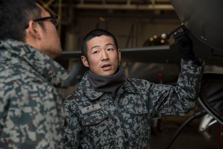 Japan Air Self-Defense Force Staff Sgts. Kenta Okazaki, left, and Narihito Tanaka, right, both 3rd Air Wing avionics technicians, discuss the proper aircraft procedures they would take for a downed aircraft at Misawa Air Base, Japan, Dec. 7, 2016. Airmen and JASDF service members participated in a bilateral exchange during a surge to gain insight on a deployed operations tempo. (U.S. Air Force photo by Airman 1st Class Sadie Colbert)