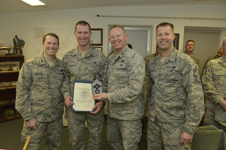Senior Master Sgt. Todd Rosenzweig, center left, 52nd Security Forces Squadron superintendent, receives notification he has been selected for promotion to chief master sergeant from Col. Joe McFall, center right, 52nd