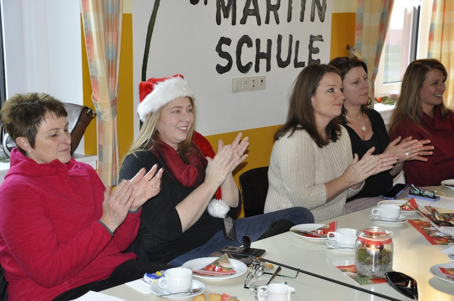 A group of 52nd Fighter Wing leadership spouses give children and helpers from the Bitburg Saint Martin school applause for performing a dance during the school's annual Saint Nicholas celebration, Dec. 5 in Bitburg. The event included a visit by Saint Nicholas, dances and singing performances by the children, as well as a gift presentation by the 52nd Fighter Wing. The celebration was attended by Saint Martin school officials, parents, 52nd Fighter Wing leadership spouses, as well as Airmen and civilians from the wing, who provided gifts to students and kindergarten children. In the summer, Spangdahlem Sabers invited the Saint Martin school to Special Children's Day at Spangdahlem AB, where they played games and spent a fun-filled time together. (U.S. Air Force photo by Iris Reiff)