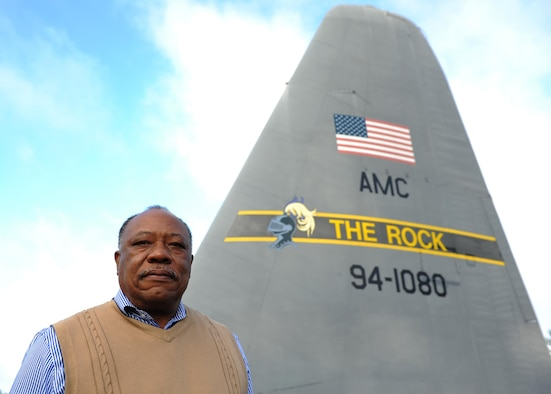 Retired U.S. Air Force Chief Master Sgt. Willie Goodwin, 19th Maintenance Group Engineering and technical services specialist, stands in front of the old tail of the last C-130E to leave Little Rock Air Force Base. The tail was removed from the C-130E and repainted to serve as a landmark in front of Hangar 1080. (U.S. Air Force photo by Airman 1st Class Grace Nichols)