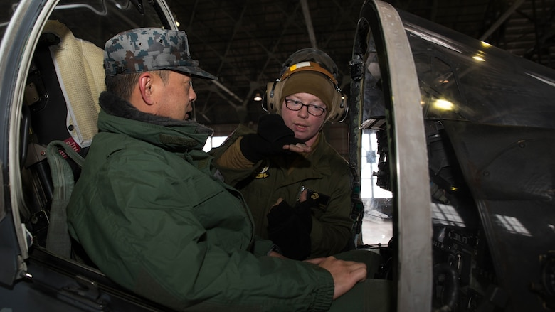 U.S. Marine Corps Lance Cpl. Jasaon Breker, a power line technician with Marine Attack Squadron (VMA) 542, explains how an AV-8B Harrier's controls work inside the cockpit to a member of the Japan Air Self Defense Force at Chitose Air Base, Japan, Dec. 9, 2016. JASDF personnel joined the VMA-542 Marines in their hangar to get a closer look and better understanding of the squadrons Harriers. (U.S. Marine Corps photo by Lance Cpl. Joseph Abrego)