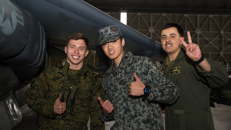 U.S. Marine Corps Lance Cpls. Austin Nazworth, left, and Breht Urzua, right, power line technicians with Marine Attack Squadron (VMA) 542, pose for a photo with a member of the Japan Air Self Defense Force at Chitose Air Base, Japan, Dec. 9, 2016. JASDF personnel joined the VMA-542 Marines in their hangar to get a closer look and better understanding of the squadrons Harriers. (U.S. Marine Corps photo by Lance Cpl. Joseph Abrego)