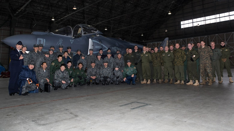 U.S. Marines with Marine Attack Squadron (VMA) 542 and Japan Air Self Defense Force personnel pose for a photo during the Aviation Training Relocation Program at Chitose Air Base, Japan, Dec. 9, 2016. JASDF personnel joined the VMA-542 Marines in their hangar to get a closer look and better understanding of the squadrons Harriers. (U.S. Marine Corps photo by Lance Cpl. Joseph Abrego)