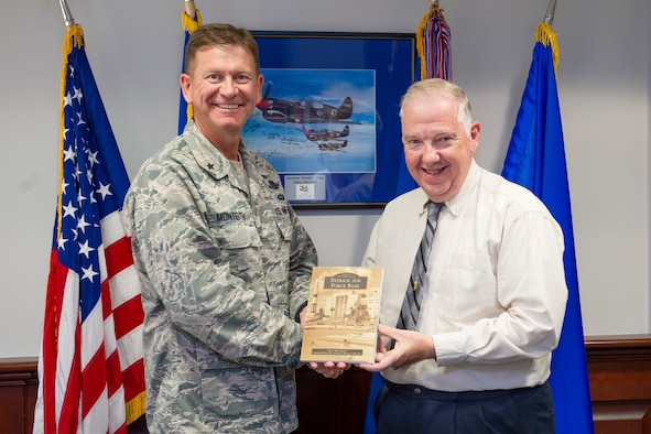 Brig. Gen. Wayne Monteith, 45th Space Wing commander, is presented with a book titled: Images of America Patrick Air Force Base by Roger McCormick, author, and volunteer at the Sands Space History Center Dec. 8, 2016, at Patrick Air Force Base, Fla. Images from military and community archives, along with private collections, are used to tell the story of this historical base, which has the responsibility of managing a military airfield and a spaceport. (U.S. Air Force photo/Matthew Jurgens)