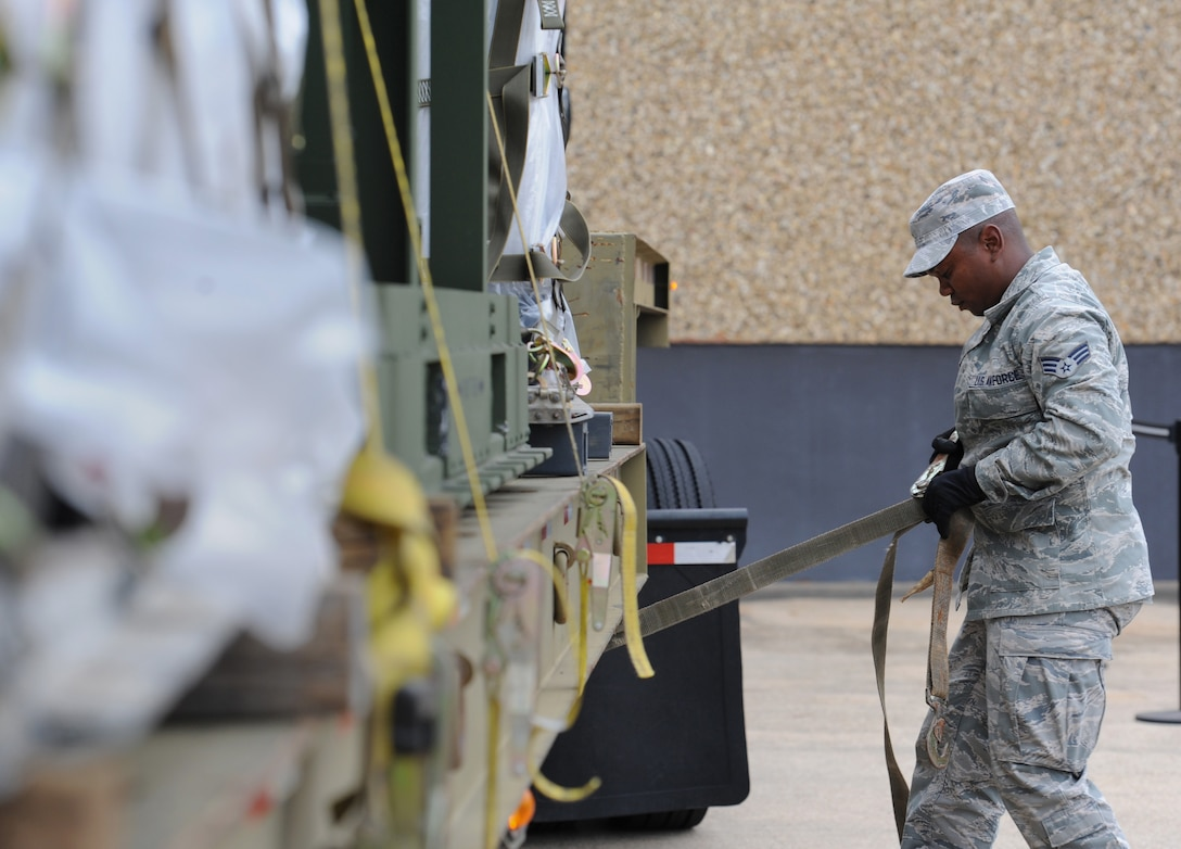 Senior Airman Mikhail Gordon, 81st Logistics Readiness Squadron vehicle operator, removes cargo straps at the supply warehouse loading docks during a deployment exercise Dec. 7, 2016, on Keesler Air Force Base, Miss. The exercise scenario tested the mission readiness of Team Keesler for simultaneous world-wide deployments. (U.S. Air Force photo by Kemberly Groue)