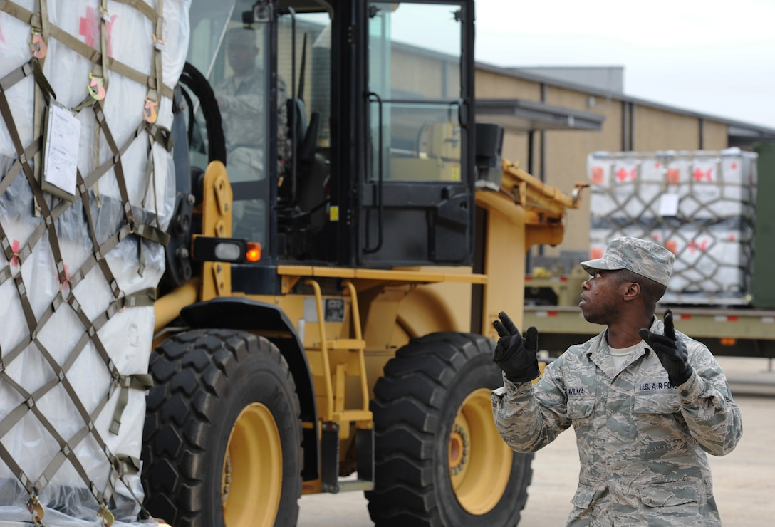 Staff Sgt. Junior Avilma, 81st Logistics Readiness Squadron vehicle operator, provides direction to Airman 1st Class David Whatley, 81st LRS vehicle maintainer, as he transports cargo at the supply warehouse loading docks during a deployment exercise Dec. 7, 2016, on Keesler Air Force Base, Miss. The exercise scenario tested the mission readiness of Team Keesler for simultaneous world-wide deployments. (U.S. Air Force photo by Kemberly Groue)