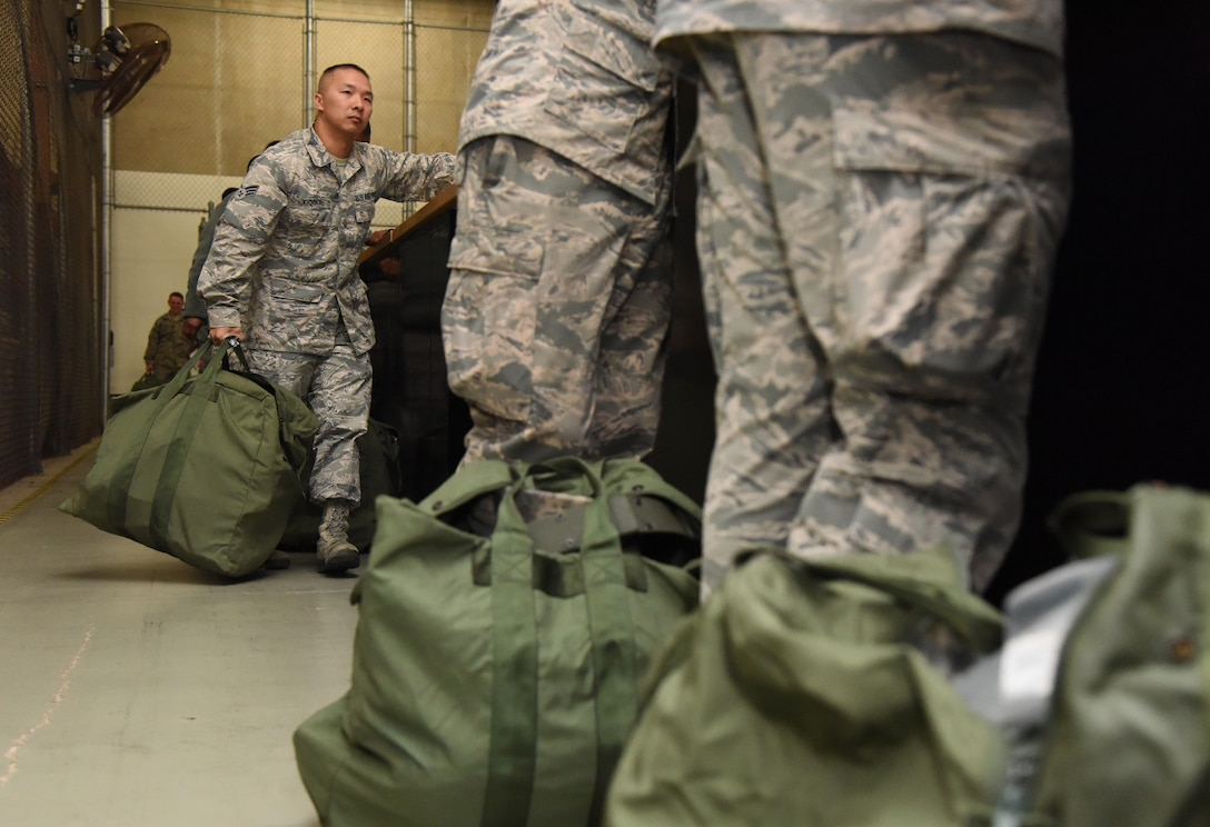 Senior Airman Xeng Xiong, 81st Force Support Squadron technician, receives mobility bag items at the supply warehouse during a deployment exercise Dec. 8, 2016, on Keesler Air Force Base, Miss. The exercise scenario tested the mission readiness of Team Keesler for simultaneous world-wide deployments. (U.S. Air Force photo by Kemberly Groue)