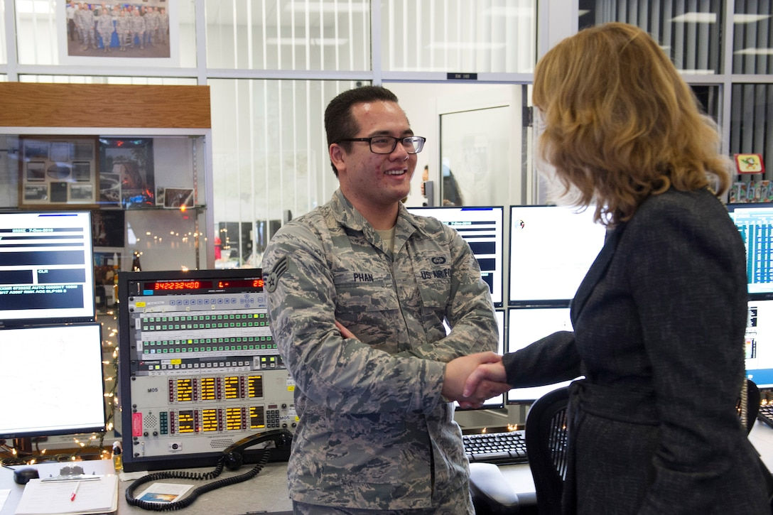 Under Secretary of the Air Force Lisa S. Disbrow coins Senior Airman Phi Phan for his dedication to the weather mission Dec. 7, 2016, at Cape Canaveral Air Force Station, Fla. The 45th Weather Squadron provides operational support to the range to ensure safe access to air and space.