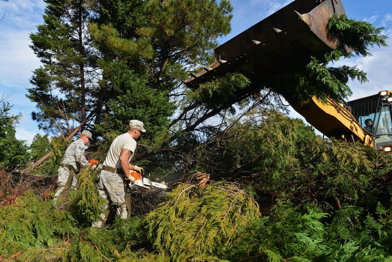Staff Sgt. Sonny Tanner and Senior Airman Reid Johanns use chainsaws to cut trees while Staff Sgt. Claudas Crenshaw operates a front-end loader to pick up the debris at Shaw Air Force Base, S.C., Dec. 5, 2016. The a 20th Civil Engineer Squadron's heavy equipment flight has cleaned up approximately 300 trees around Shaw that were damaged or uprooted during Hurricane Matthew. (U.S. Air Force photo/Airman 1st Class Destinee Sweeney)