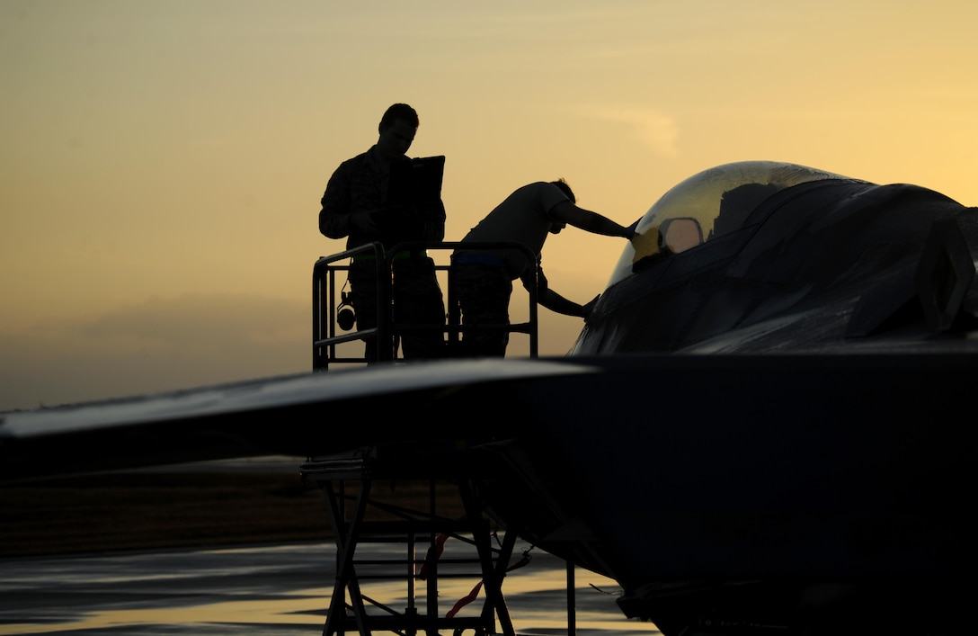 Air Force maintainers from the 325th Maintenance Squadron inspect and wipe off the cockpit of an F-22 Raptor on the flightline at Tyndall Air Force Base, Fla., after a thunderstorm Dec. 5, 2016. The F-22 and other aircraft continued operations after the storm during Checkered Flag 17-1. (U.S. Air Force photo/Senior Airman Solomon Cook)