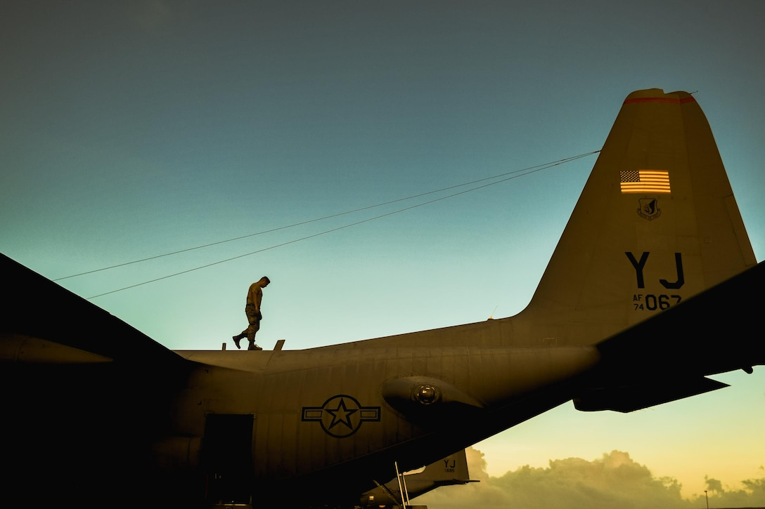 An Airman from the 374th Maintenance Squadron checks a C-130 Hercules for potential damage during Operation Christmas Drop 2016 at Andersen Air Force Base, Guam, Dec. 6, 2016. This year marks the 65th year of Operation Christmas Drop, which began in 1952, making it the world's longest-running airdrop mission. (U.S. Air Force photo/Senior Airman Delano Scott)