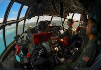 Aircrew aboard a C-130 Hercules assigned to the 36th Airlift Squadron circle a Micronesian Island Dec. 5, 2016. The crew was practicing airdrop procedures during Operation Christmas Drop. Each year Operation Christmas Drop provides aid to over 30,000 islanders in the Pacific. (U.S. Air Force photo/Senior Airman Elizabeth Baker)