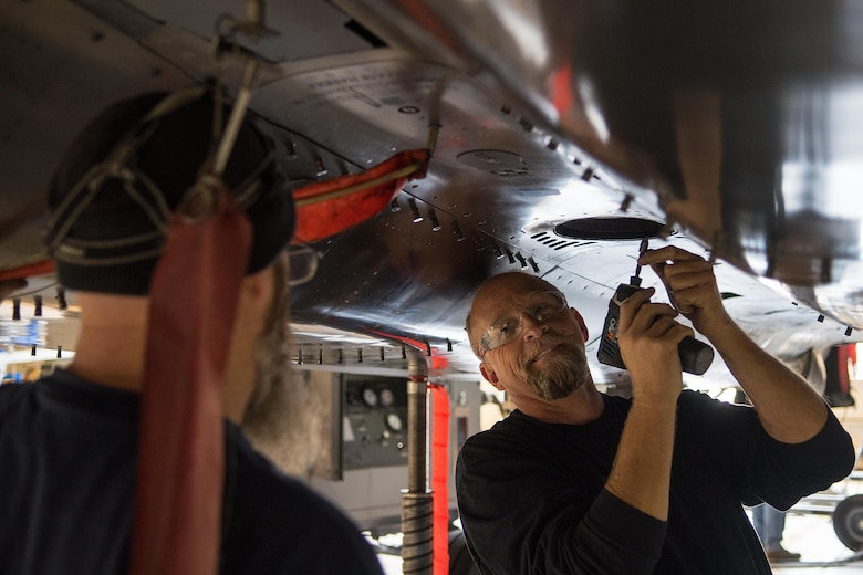 Charles Loy (right), Boeing Co. aircraft mechanic, begins to remove a panel off an F-15E Strike Eagle, Nov. 1, 2016, at Seymour Johnson Air Force Base, North Carolina. The F-15E is receiving a Radar Modernization program; it's first major upgrade of its radar system in more than 20 years. (U.S. Air Force photo by Airman Shawna L. Keyes)