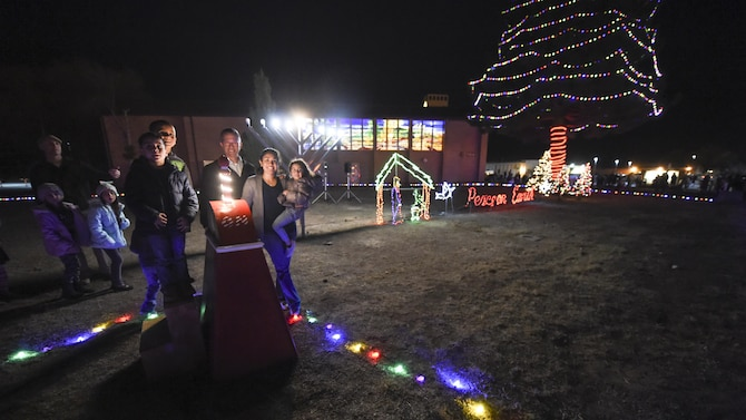 Col. Houston Cantwell, the 49th Wing commander along with Vanessa Bordelon, wife of deployed member from the 2nd Lt. Dustin Bordelon, 49th Aircraft Maintenance Squadron and their two sons stand next to decorative holiday lights during the base menorah and tree lighting ceremony Dec. 7, at the base chapel. Santa made an appearance on a fire truck and children sang holiday-themed songs during the ceremony. (U.S. Air Force photo by Staff Sgt. Stacy Jonsgaard)