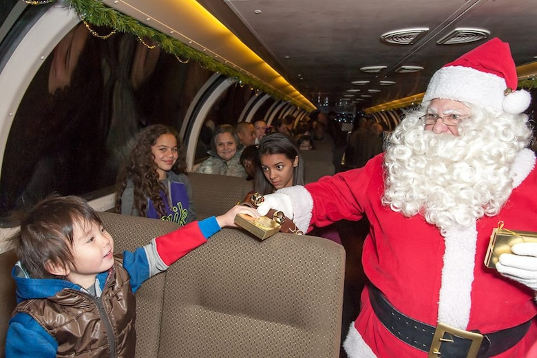 Santa Claus gives a young passenger aboard the Holiday Express a small gift. Burlington Northern and Santa Fe Railway Company, a nationwide freight transportation company, has been running its Holiday Express for the past eight years to give members of the military and their families the experience of riding a train. About 300 people experienced the holiday train ride.