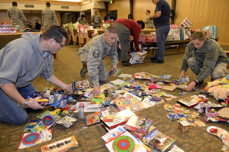 (Left to right) John Pascowitz, volunteer, Master Sgt. Jason Franklin, 75th Force Support Squadron, and Airman 1st Class Morgan Matteson, 388th Fighter Wing, sort donated toys Dec. 7 at the Hill AFB Chapel. The toys, collected during Operation Home Front, will be distributed as part of the Angel Tree program to military families. (U.S. Air Force photo by Todd Cromar)