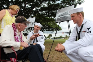 PEARL HARBOR, Hi. (Dec. 7, 2016) Former USS Maryland (BB-46) crew member and Pearl Harbor survivor Electricians Mate Floyd Welch and his daughter Laurie Broglio, share memories with Petty Officer 1st Class Thomas McMillian and Petty Officer 2nd Class Kristian Cheeks during the Dec. 7 USS Oklahoma Memorial Ceremony on Ford Island.  Petty Officers McMillian and Cheeks, both assigned to Pearl Harbor Naval Shipyard & Intermediate Maintenance Facility (PHNSY & IMF) were part of a detail which displayed photos tracking the salvage of USS Oklahoma following the attacks of Dec. 7, 1941.