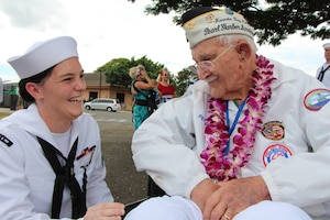 PEARL HARBOR, Hi. (Dec. 7, 2016) Seaman Rachel Johnson listens as former USS Maryland (BB-37) crew member and Pearl Harbor survivor Peter Nichols, share memories during the Dec. 7 USS Oklahoma Memorial Ceremony on Ford Island.  Seaman Johnson, assigned to Pearl Harbor Naval Shipyard & Intermediate Maintenance Facility (PHNSY & IMF) was part of a detail which displayed photos tracking the salvage of USS Oklahoma following the attacks of Dec. 7, 1941.