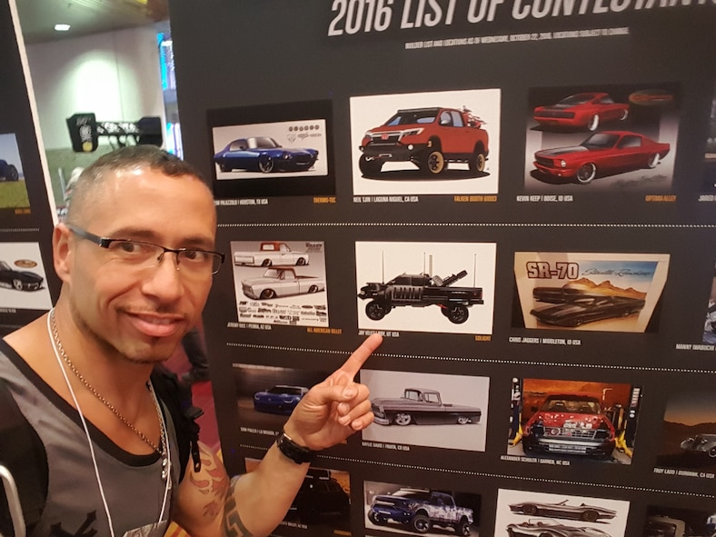 Jason Velez points to a picture of his custom built Dodge Ram 2500. Velez, a retired Airman,  rebuilt the truck to resemble a vehicle halfway between a personal vehicle and tactical military vehicle. Velez's truck was on exhibit in the Battle of the Builder at the 2016 Specialty Equipment Market Association (SEMA) Show in Las Vegas in November, the foremost automotive specialty products trade event worldwide. (Courtesy photo)