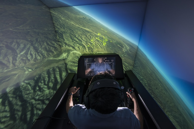 Zach Demers, an aerospace engineer, demonstrates the Automatic Ground Collision Avoidance System (Auto GCAS) in an F-16 flight simulator at the Air Force Research Laboratory, Wright-Patterson Air Force Base, Ohio, April 18. Auto GCAS, which constantly compares the aircraft's speed and position to a digital terrain map and will automatically take control if it detects an imminent ground collision, is credited with saving the lives of four pilots. (U.S. Air Force photo/Master Sgt. Brian Ferguson)