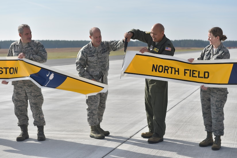 U.S. Air Force Col. Jimmy Canlas 437 Airlift Wing commander, middle right and U.S. Air Force Col. Richard Mathews, 628th Mission Support Group commander, middle left, cut a banner marking the completion of repairs to the North Auxiliary Airfield Runway in North, South Carolina, Dec. 8, 2016. Repairs included approximately 21,000 tons of asphalt repurposed as the foundation below the new concrete, 66,000 linear feet of wire, a new runway lighting system and an additional 36,000 square yards of asphalt shoulder to the landing zone.