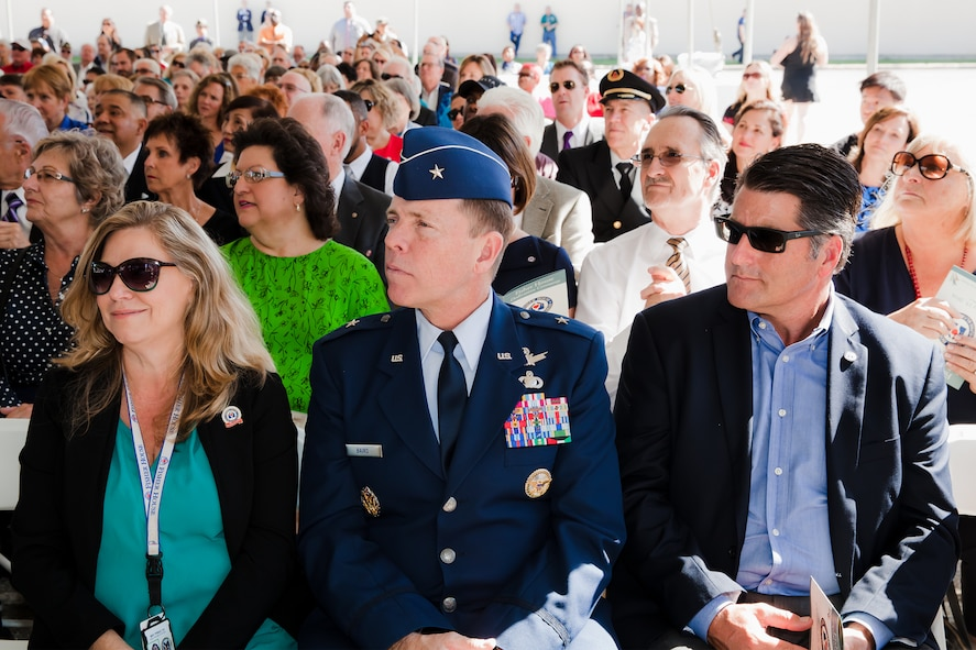 Brig. Gen. Mark Baird, vice commander of the Space and Missile Systems Center at Los Angeles Air Force Base in El Segundo, California, seated with Lana Toenjes, VA Long Beach Fisher House manager, and Drew Hatcher of the Masco Corporation Foundation, listens to remarks by Fisher House Foundation president David Coker during the dedication ceremony Oct. 19 at the VA Long Beach Medical Center. General Baird attended the ribbon-cutting and housewarming of the sixth and newest Fisher House to open in California as a representative of the only active duty military installation within the greater Los Angeles metropolitan area. (Courtesy photo/ VA Long Beach Healthcare System)