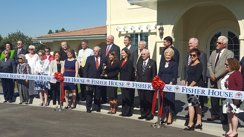 Tracye Davis, acting director of the Veterans Affairs Long Beach Healthcare System, holding scissors, and Fisher House Foundation president David Coker, left of Davis, with community supporters get ready to cut the ceremonial ribbon signifying the sixth and newest Fisher House to open in California during a dedication ceremony Oct. 19 at the VA Long Beach Medical Center. (Courtesy photo/ Fisher House Foundation)