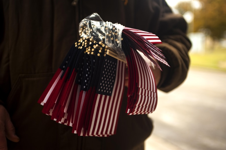 A volunteer holds miniature American flags during the Hero's Hunt Parade at Santa Fe Park in San Angelo, Texas, Dec. 8, 2016. Multiple volunteers walked the parade path handing out flags for attendees to take and wave to the parade members. San Angelo hosts the Hero's Hunt Parade for veterans from all over Texas to honor them for their service. (U.S. Air Force photo by Senior Airman Scott Jackson/released)