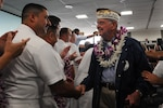 Retired Navy Capt. Bob Batterson is greeted by a sailor after arriving at Honolulu International Airport on an honor flight, Dec. 3, 2016. Batterson traveled from Los Angeles on the flight with more than 100 other World War II veterans for commemorations for the 75th anniversary of the attack on Pearl Harbor. DoD photo by Lisa Ferdinando