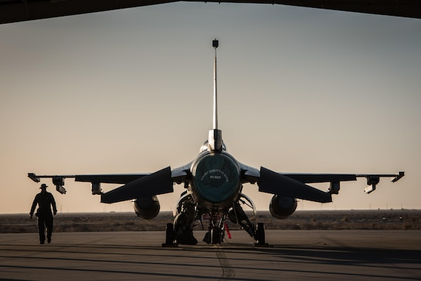 A crew chief with the 407th Expeditionary Aircraft Maintenance Squadron walks past an F-16 Fighting Falcon assigned to the 134th Expeditionary Fighter Squadron at the 407th Air Expeditionary Group, Southwest Asia, Dec. 10, 2016. About 300 Airmen from the 158th Fighter Wing of the Vermont Air National Guard comprise the units. (U.S. Air Force photo by Master Sgt. Benjamin Wilson)