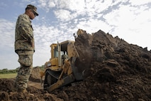 Cpl. Andrew Bastian, a heavy equipment advisor with Special Purpose Marine Air-Ground Task Force Crisis Response-Africa, watches as a soldier with the Uganda People's Defense Force uses a bulldozer to construct a berm for the new forward operating base at Camp Singo, Uganda, Nov. 16, 2016. Marines with SPMAGTF-CR-AF taught classes and participated in practical application exercises with UPDF soldiers during the nine-week training mission. (U.S. Marine Corps photo taken by Cpl. Alexander Mitchell/released)