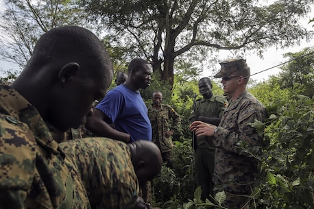 Cpl. Timothy Dykes, a communications advisor with Special Purpose Marine Air-Ground Task Force Crisis Response-Africa, talks to a soldier with the Uganda People's Defense Force about setting up radio antennas at Camp Singo, Uganda, Nov. 17, 2016. Marines with SPMAGTF-CR-AF taught classes and participated in practical application exercises with UPDF soldiers during the nine-week training mission. (U.S. Marine Corps photo taken by Cpl. Alexander Mitchell/released)