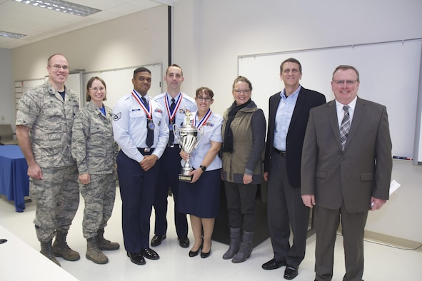 Col. Alden Hilton, commander of the 711th Human Performance Wing's U.S. Air Force School of Aerospace Medicine, poses with the judges and winners of the school's third annual SAM-Tastic instructional excellence competition. Left to right are: Hilton; Col. Elena Oberg, 88th Air Base Wing vice commander and SAM-Tastic judge; Staff Sgt. Christopher Cameron, USAFSAM Occupational and Environmental Health Department instructor; Staff Sgt. Jonathan Cavier, USAFSAM Occupational and Environmental Health Department instructor; Staff Sgt. Barbara Rucker, USAFSAM Occupational and Environmental Health Department instructor; Tammy Bugher, Air Force Institute of Technology School of Systems and Logistics director of Instructional Systems and SAM-Tastic judge; Tim Sakulich, 711 HPW vice director and SAM-Tastic judge; and John Duren, SAM-Tastic program manager. (U.S. Air Force photo/David Snedigar)