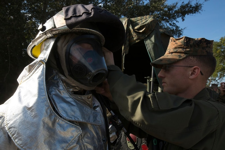 Lance Cpl. Brandon Black is inspected by Cpl. Darrell Powers during a timed training evolution being conducted aboard Marine Corps Auxiliary Landing Field Bogue, N.C., Nov. 30, 2016. Aircraft firefighting and rescue specialists assigned to Marine Wing Support Squadron 271, Marine Aircraft Group 14, 2nd Marine Aircraft Wing, conducted military occupational specific training during a two-week field exercise with the squadron. Black and Powers are aircraft firefighting and rescue specialists assigned to MWSS-271. (U.S Marine Corps photo by Sgt. N.W. Huertas/ Released)