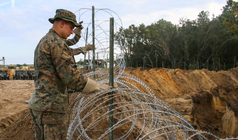 Lance Cpl. Travis Debello fixes concertina wire around the perimeter of an encampment established by Marines with Marine Wing Support Squadron 271, Marine Aircraft Group 14, 2nd Marine Aircraft Wing, during a two-week field exercise aboard Marine Corps Auxiliary Landing Field Bogue, N.C., Nov. 30, 2016. Debello said conducting field exercises like this is good for the Marines, because it allows them to gain hands on experience and test their strengths in a field setting. Debello is a combat engineer assigned to Engineer Company, MWSS-271. (U.S. Marine Corps photo by Sgt. Austin Long/ Released)