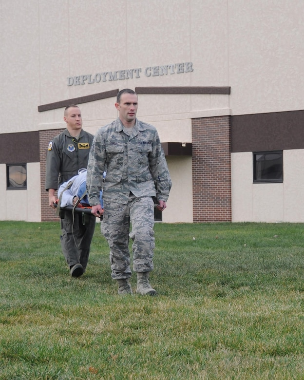 U.S. Air Force Capt. Andrew Schaar and Staff Sgt. Merlin Jewell, medical personnel assigned to the 393rd Bomb Squadron, carry a volunteer simulating a severe injury during a total force mass casualty exercise at Whiteman Air Force Base, Mo., Dec. 3, 2016. Emergency personnel arrived on the scene, triaged the victims and transported them to the clinic to be decontaminated and treated. (U.S. Air Force photo/Senior Airman Missy Sterling)