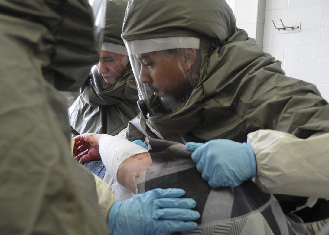 U.S. Air Force Airman 1st Class Chris Stangl, right, a public health technician, and Senior Airman Dylan Kielcheski, an aerospace medical technician, both with the 509th Medical Operations Squadron, help hold a volunteer victim on their side to decontaminate all areas of the victim during a total force mass casualty exercise at Whiteman Air Force Base, Mo., Dec. 3, 2016. Volunteer victims were brought through a decontamination line before being admitted into the clinic. (U.S. Air Force photo/Senior Airman Missy Sterling)