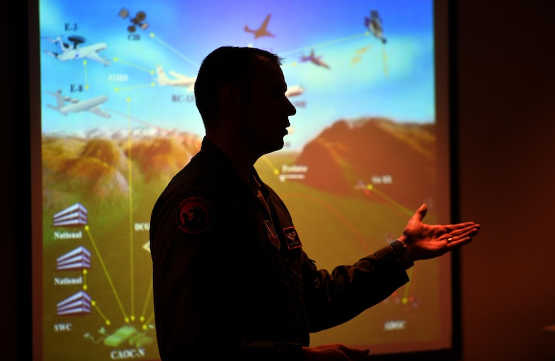 Capt. Tim Kenny, Chief of Central Flight Instructors Course with the 338th Combat Training Squadron, gives a briefing to military spouses as to the overall mission of the 55th Wing during a Spouse Appreciation Night held Dec. 7, 2016, at Offutt Air Force Base, Neb. Following the briefing, spouses were given the chance to pilot a flight simulator before getting to tour one of the aircraft associated with the wing. (U.S. Air Force photo by Josh Plueger)
