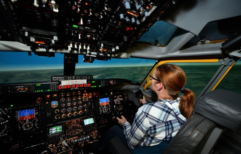 Chelsea Day, wife of Capt. Michael Day with the 55th Operational Support Squadron, pilots an Operational Flight Trainer simulator as part of a Spouse Appreciation Night held Dec. 7, 2016, at Offutt Air Force Base, Neb. The OFT3 simulator provides realistic flight training for pilots prior to piloting the different aircraft at Offutt AFB. (U.S. Air Force photo by Josh Plueger)