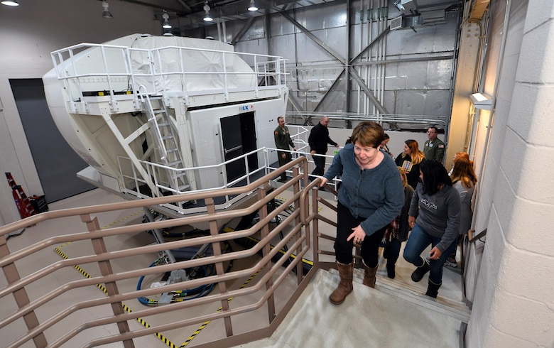 Spouses of military Airmen exit the Operational Flight Trainer simulator, as part of a Spouse Appreciation Night held Dec. 7, 2016, at Offutt Air Force Base, Neb. The OFT3 simulator provides a variety of realistic simulations to test new pilots and navigators prior to flying a real RC-135 aircraft. (U.S. Air Force photo by Josh Plueger)
