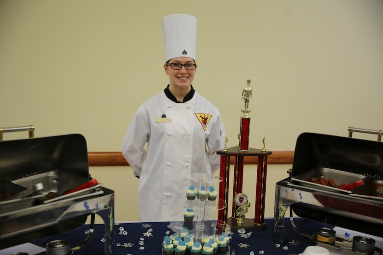 Sgt. Destany Weatherwax poses behind her first place trophy and winning meal after the Chef of the Quarter competition aboard Marine Corps Air Station Cherry Point, Dec. 8, 2016. The competition is designed to test participating food service specialists' cooking abilities and skill sets in several areas, such as preparation and display. Weatherwax prepared the winning meal including the main course of an apple-glazed corned beef with roasted potatoes and carrots. Weatherwax is a food service specialist assigned to Marine Wing Support Squadron 271, Marine Aircraft Group 14, 2nd Marine Aircraft Wing. (Marine Corps photo by Lance Cpl. Cody Lemons/Released)