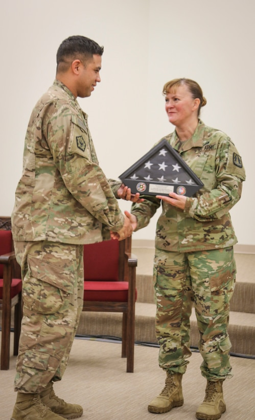Army Reserve Staff Sgt. Mathew J. Tolbe, an information technology specialist from Waianae, Hawaii, assigned to Detachment 10, 335th Signal Command (Theater) receives a Welcome Home Warrior flag and display case from Brig. Gen. Nikki Griffin-Olive, deputy commanding general of sustainment, 335th SC (T) during a welcome home warrior ceremony at the North Fort Hood Chapel Dec. 11.  Tolbe and nearly 70 other Army Reserve Soldiers from Det. 10 recently returned from a nine month deployment to Kuwait in support of Operations Freedom Sentinel and Spartan Shield.