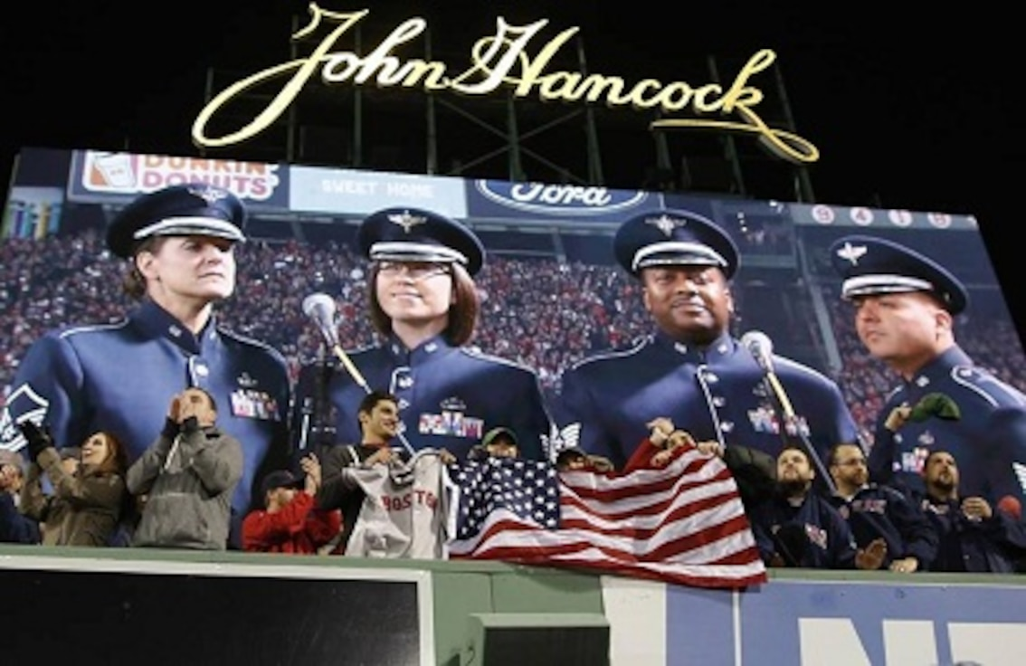 "MSgt Jennifer Dashnaw, Technical Sergeant Niko Ellison, Technical Sergeant Quez Vasquez and Staff Sergeant Rachel Webber of the U.S.A.F. Heritage of America Band sing ""God Bless America"" during the seventh-inning stretch of game six of the World Series (Daily Press/ October 30, 2013)"