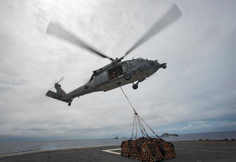 In this file photo,  an MH-60S Sea Hawk, assigned to Helicopter Sea Combat Squadron (HSC) 25, picks up cargo pallets from the flight deck of amphibious assault ship USS Bonhomme Richard (LHD 6) during a replenishment at sea (RAS), Sept. 22, 2016. Bonhomme Richard, flagship of the Bonhomme Richard Expeditionary Strike Group, is operating in the Philippine Sea in support of security and stability in the Indo-Asia Pacific region.